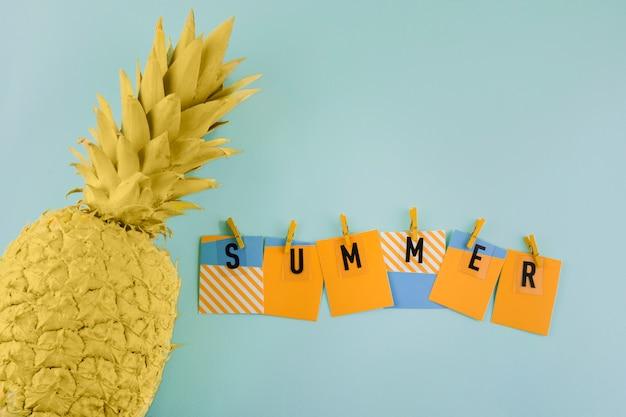 Rótulo de verão com prendedor de papel perto do abacaxi amarelo pintado sobre fundo azul Foto gratuita