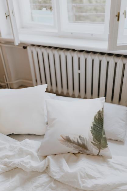 Roupa de cama branca em um quarto Foto gratuita