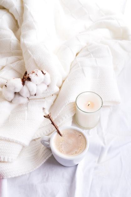 Roupa de cama com uma manta de malha fofa e xícara de café, flores de algodão e velas. Foto Premium
