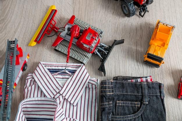 Roupa de menino perto de conjunto de brinquedo do carro. camisa listrada, calça jeans perto de carros amarelos e vermelhos. Foto Premium