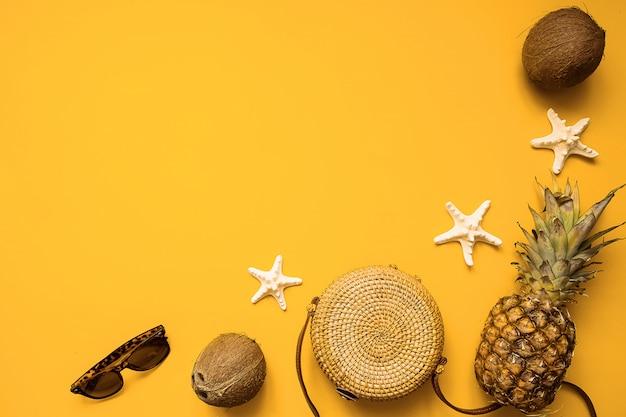 Roupa de moda feminina verão colorido plana leigos. saco de bambu, óculos de sol, coco, abacaxi e estrela do mar sobre fundo amarelo, vista superior Foto Premium