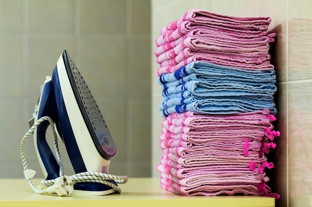 Roupa de passar roupa com gerador de vapor. uma pilha de toalhas passadas ao lado do ferro. placa de teflon única coberta com pequenos orifícios. Foto Premium