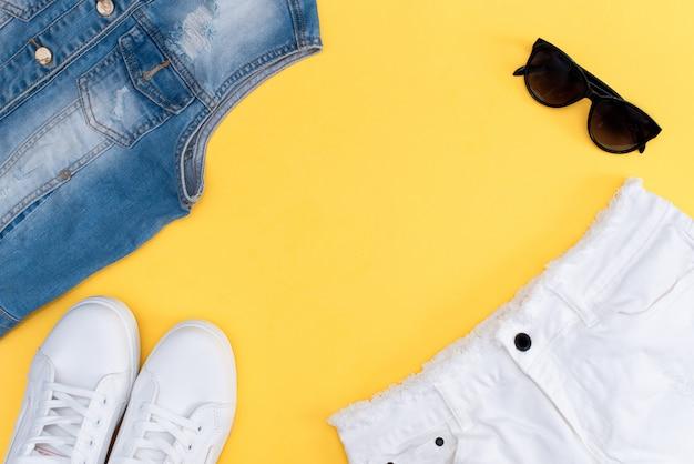 Roupa de verão: camiseta listrada, shorts jeans e snickers brancos. Foto Premium
