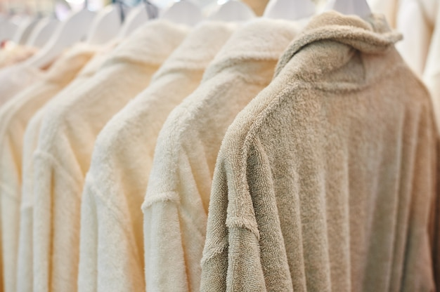 Roupão de banho branco pendurado no armário de madeira Foto Premium