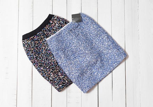Roupas da moda. mini-saias de brilho preto e azul em pranchas de madeira branca Foto Premium