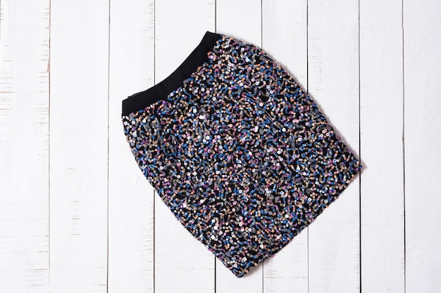 Roupas da moda. mini saias de brilho preto em pranchas de madeira branca Foto Premium
