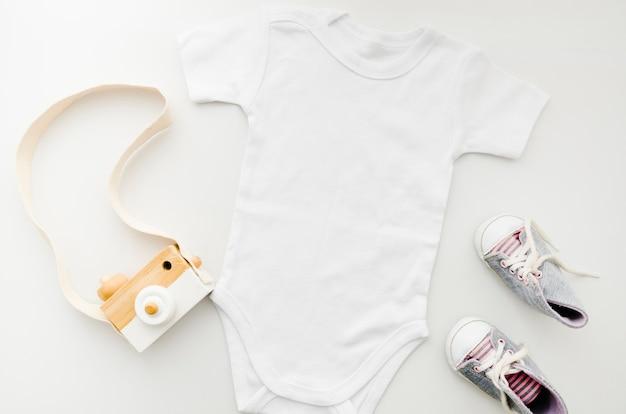 Roupas de bebê plana leigos com câmera fotográfica Foto gratuita