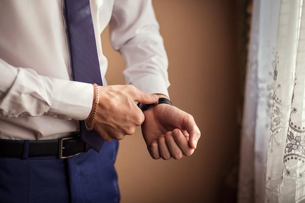 Roupas de relógio de empresário, empresário, verificando o tempo em seu relógio de pulso. mão de homem com relógio, relógio de mão de homem, honorários do noivo, preparação do casamento, preparação para o trabalho Foto Premium