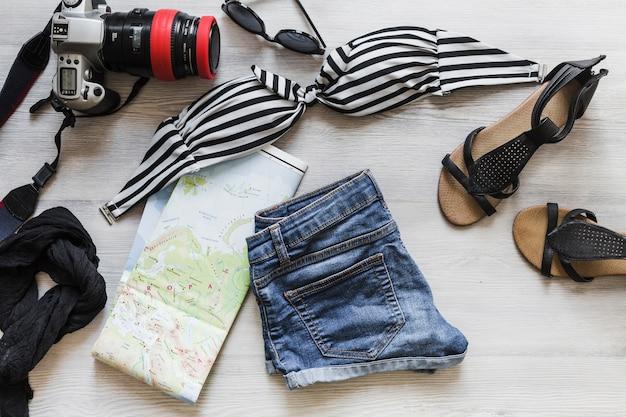 Roupas de viagem femininas com câmera e mapa na mesa Foto gratuita