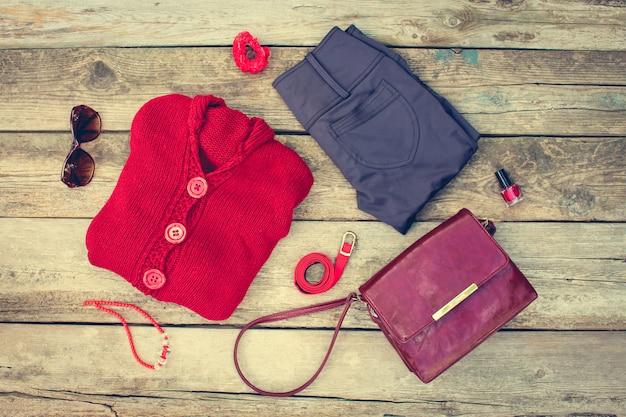 Roupas e acessórios femininos de outono: blusa vermelha, calça, bolsa, miçangas, óculos de sol, esmaltes, faixa de cabelo, cinto em fundo de madeira. imagem enfraquecida. Foto Premium