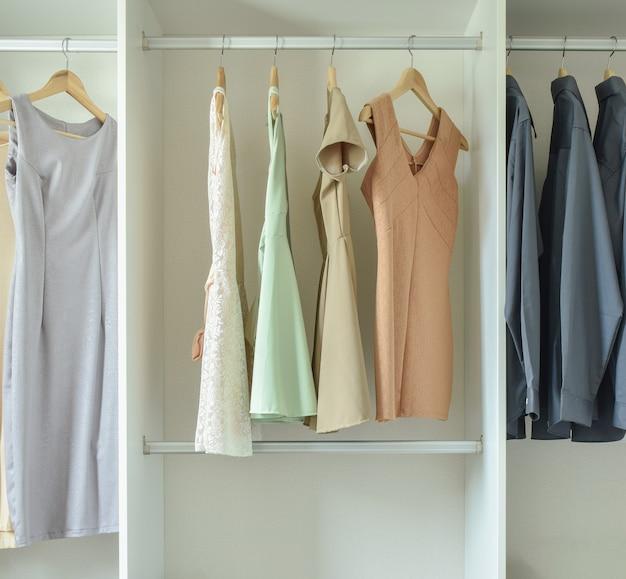 Roupas masculinas e femininas, penduradas em cabides no guarda-roupa Foto Premium