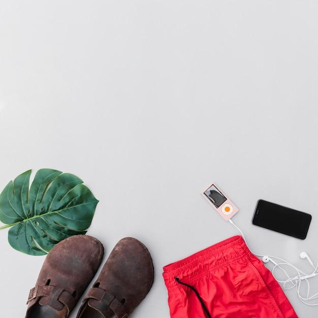 Roupas, par de sapatos, folha, celular e mp3 player em fundo cinza Foto gratuita