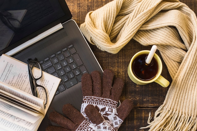 Roupas quentes e bebida quente perto de laptop e livro Foto gratuita