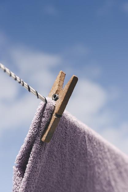 Roupas secando ao ar livre. prendedor de papel de madeira de close-up. roupas penduradas em corda. Foto Premium