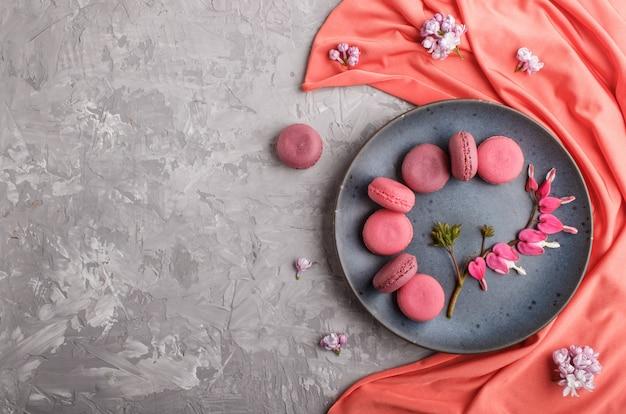 Roxo e rosa macaron ou bolos macaroon na placa cerâmica azul com têxteis vermelho Foto Premium