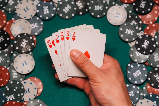 Royal flush no jogo de poker nas mãos do jogador no fundo de uma mesa verde com fichas de jogos Foto Premium