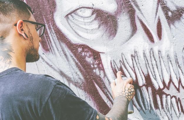 Rua grafiteiro pintando com um spray de cor um grafite de caveira monstro escuro na parede Foto Premium