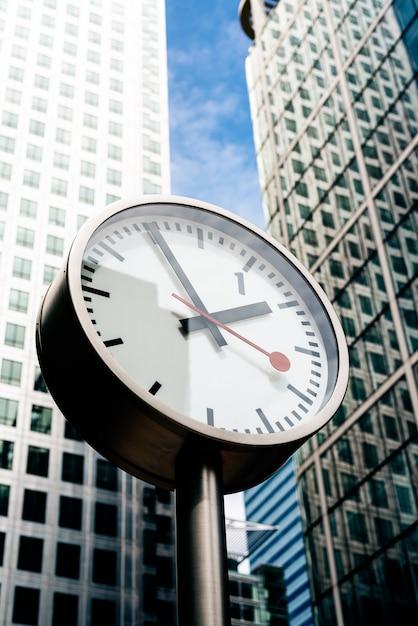 Rua relógio com prédio alto no fundo Foto Premium