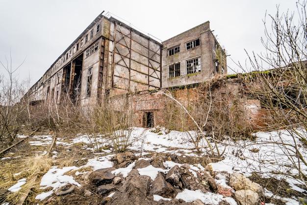 Ruínas de concreto no distrito industrial. ruínas de edifícios abandonados de fábrica ou armazém industrial quebrado velho após desastre Foto Premium