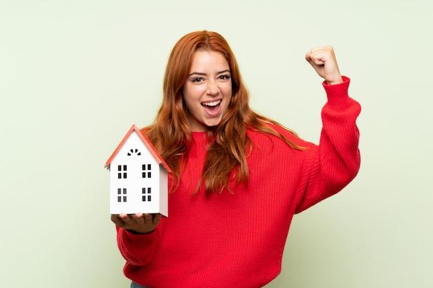 Ruiva adolescente com camisola sobre verde isolado, segurando uma casinha Foto Premium