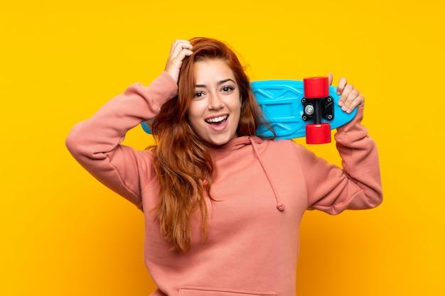 Ruiva adolescente com skate sobre amarelo isolado Foto Premium