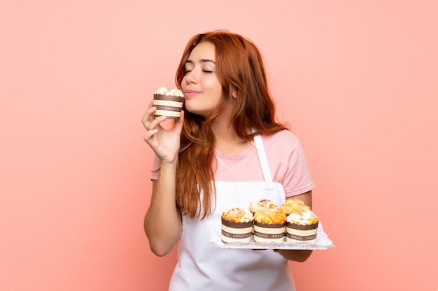 Ruiva adolescente segurando muitos mini bolos diferentes sobre rosa isolado Foto Premium