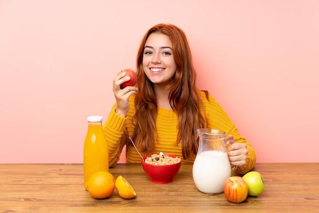 Ruiva adolescente tomando café da manhã em uma mesa | Foto Premium
