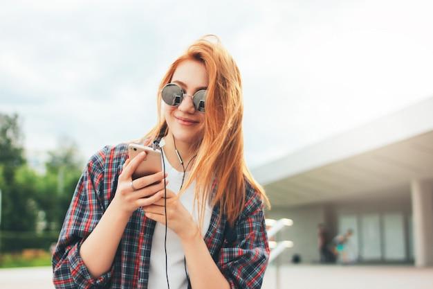 Ruiva atraente garota sorridente em óculos de sol redondos com telefone nas mãos em roupas casuais, ouvindo música Foto Premium