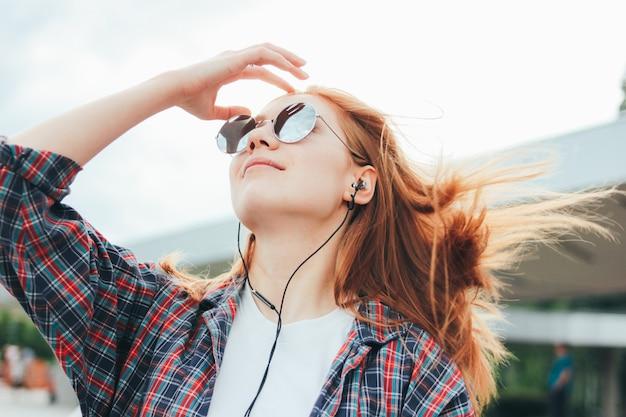 Ruiva atraente garota sorridente em óculos de sol redondos com telefone nas mãos em roupas casuais Foto Premium