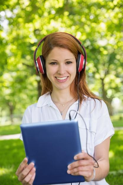 Ruiva bonita usando seu tablet pc enquanto ouve música no parque Foto Premium