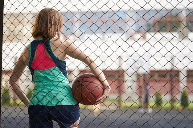 Ruiva caucasiana magra em pé perto da cerca da quadra de basquete de rua ao ar livre, segurando uma bola e observar um jogo Foto Premium