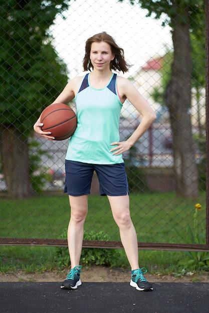 Ruiva em pé na quadra de basquete ao ar livre, segurando uma bola e sorrindo Foto Premium