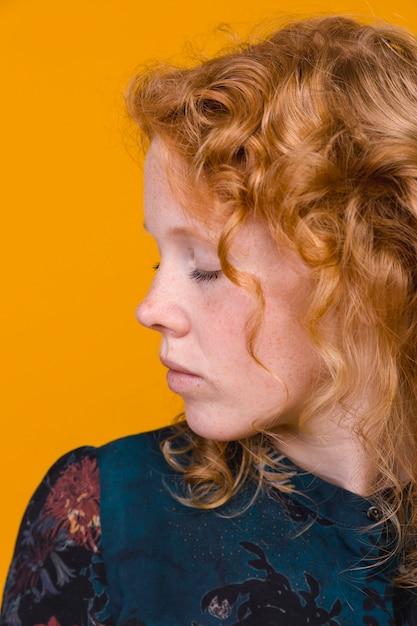 Ruiva jovem a afastar-se com os olhos fechados Foto gratuita