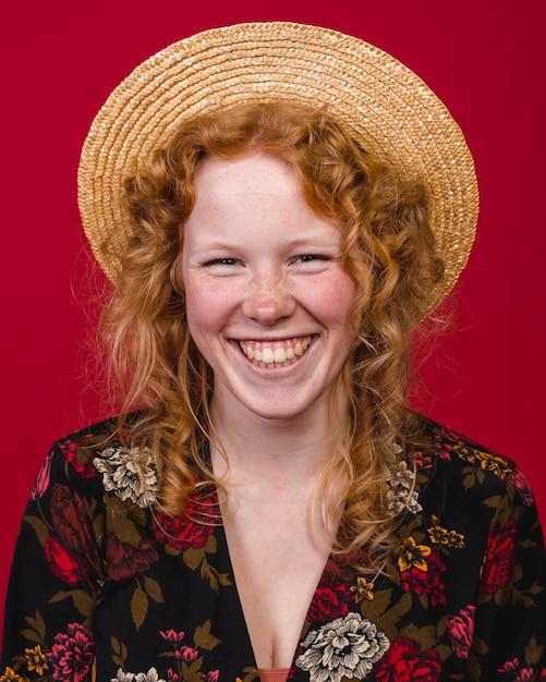 Ruiva jovem fêmea sorrindo amplamente na câmera Foto gratuita