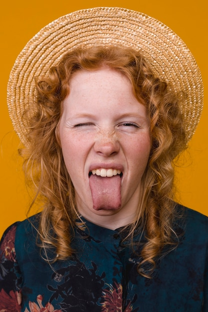 Ruiva jovem sardenta mulher mostrando a língua Foto gratuita