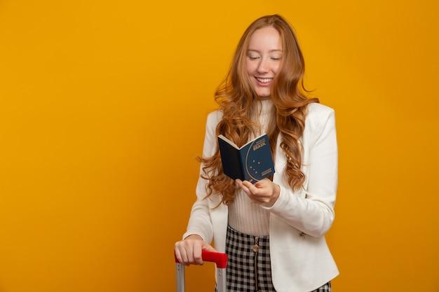 Ruiva linda garota de cabelos em viagem. próxima viagem. menina, segurando o passaporte brasileiro. em amarelo. Foto Premium