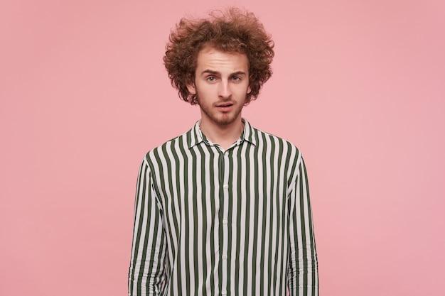 Ruivo jovem cacheado atraente com penteado casual, mantendo as mãos abaixadas enquanto posa sobre a parede rosa, olhando para a câmera com rosto calmo e testa enrugada Foto gratuita