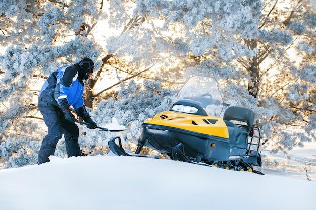Rússia, sibiria, 24 de janeiro de 2019: homem com snowmobile furado. nascer do sol, dia de inverno do sol. diversão de inverno para o homem. Foto Premium