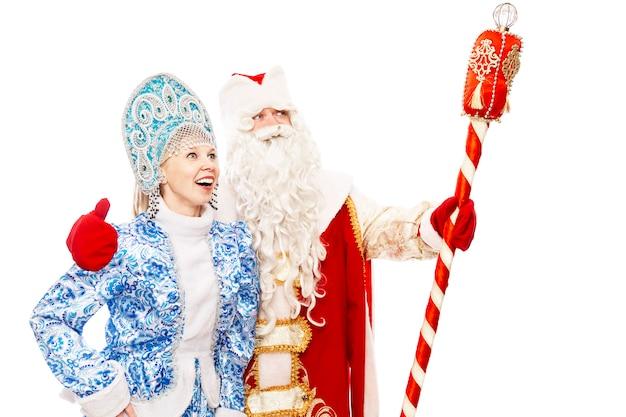 Russo papai noel com uma equipe com uma donzela de neve sorrindo e olhando para a distância. isolado sobre o fundo branco espaço para texto. Foto Premium