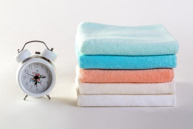 Sabão cerâmico, frascos do champô e toalhas brancas do algodão no fundo branco. Foto Premium