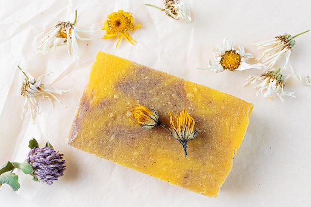 Sabonete artesanal natural com extrato de flor de camomila. ao redor são flores secas. Foto Premium