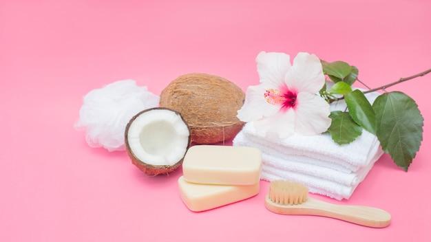 Sabonete; escova; coco; esponja; flor e toalhas no pano de fundo rosa Foto gratuita