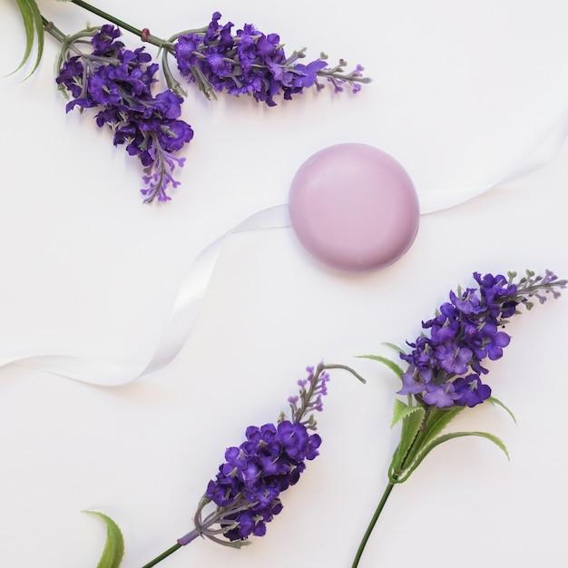 Sabonete; flores de lavanda e fita em fundo branco Foto gratuita