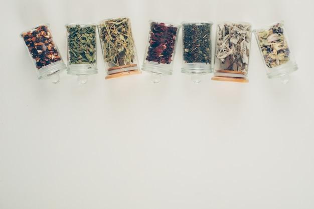 Sabores de chá em pequenos frascos. configuração plana. Foto gratuita