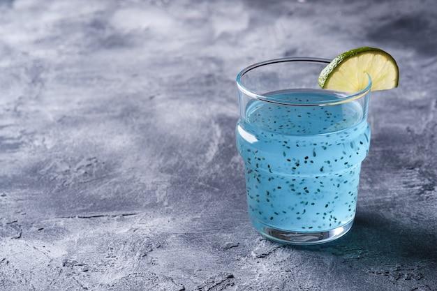 Saborosa bebida de cor azul com sementes de manjericão chia e fatia de limão cítrico em vidro Foto Premium