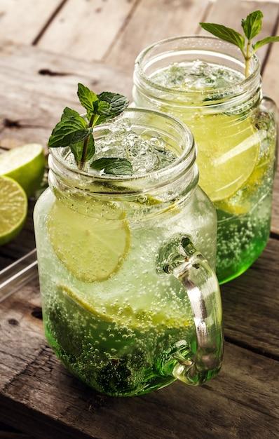 Saborosa limonada de bebida fresca fria com limão, hortelã, gelo e lima em vidro na mesa de madeira. fechar-se. Foto gratuita