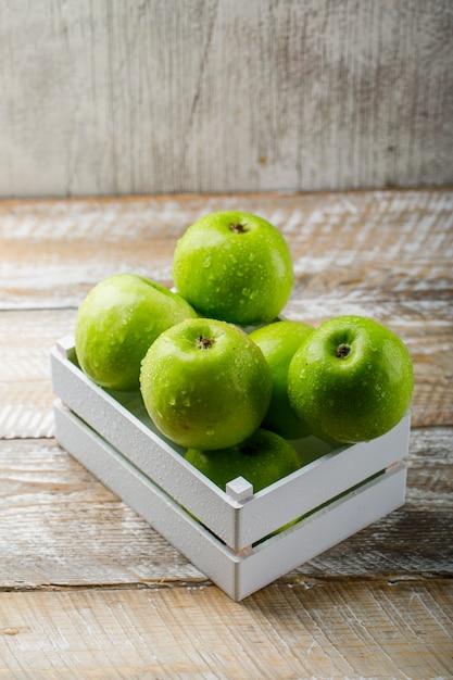Saborosas maçãs verdes em uma caixa de madeira na luz de madeira e fundo do grunge. Foto gratuita