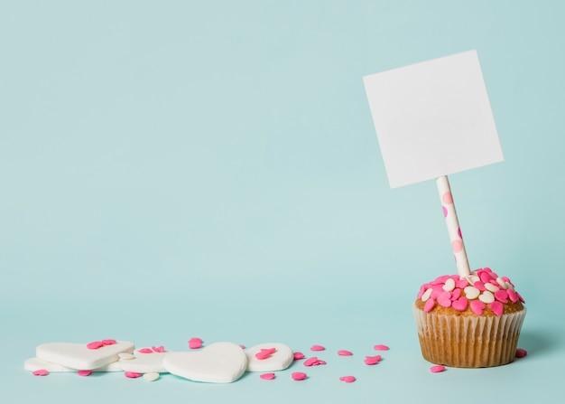 Saboroso bolo com tag na vara e corações decorativas Foto gratuita