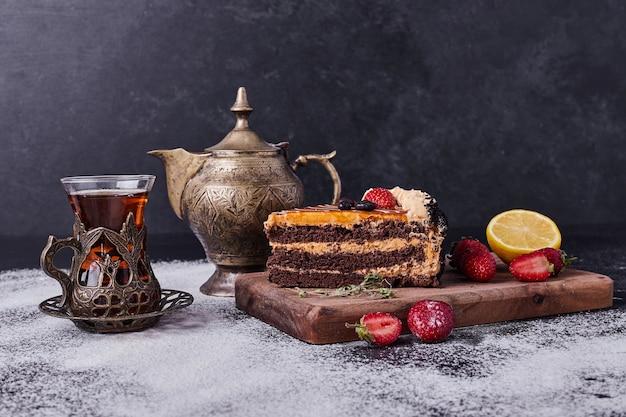 Saboroso bolo de chocolate com jogo de chá e frutas em fundo escuro. Foto gratuita