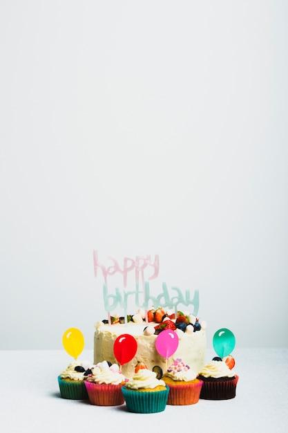 Saboroso bolo fresco com frutas e feliz aniversário título perto conjunto de bolinhos Foto gratuita
